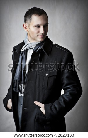 Fashion portrait of handsome young man model in black coat for autumn and spring