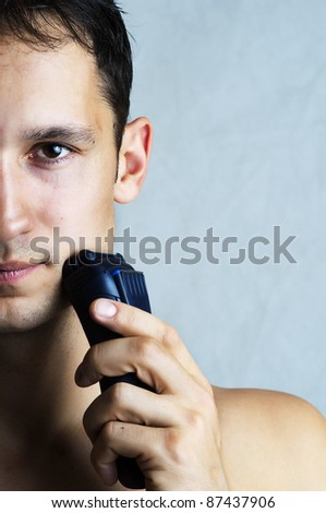 Fashion portrait of man shaving chin and cheek by electric shaver. Male hygiene. Copy space for your text