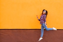 Fashion portrait of pretty smiling and jumping woman in sunglasses with smartphone against the colorful orange wall. Copyspace