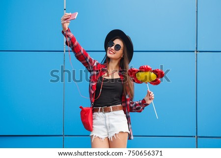 Fashion portrait of pretty smiling and woman in sunglasses with smartphone against the colorful blue wall. Make selfie with balloon in her hand