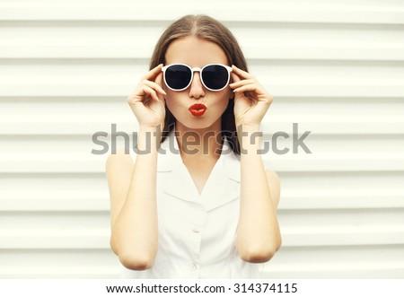 Fashion portrait of pretty young woman in white sunglasses