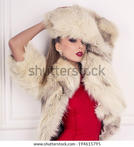 fashion portrait of sexy blond woman in elegant red dress and fur coat