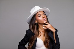 Fashion Portrait of stylish black woman in a Hat. Makeup - beige Lips. Beautiful model African American girl posing in a white stylish hat in the studio