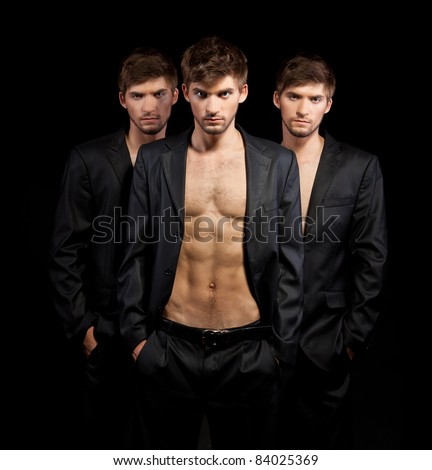 the three young beautiful brother twins men model over gray background