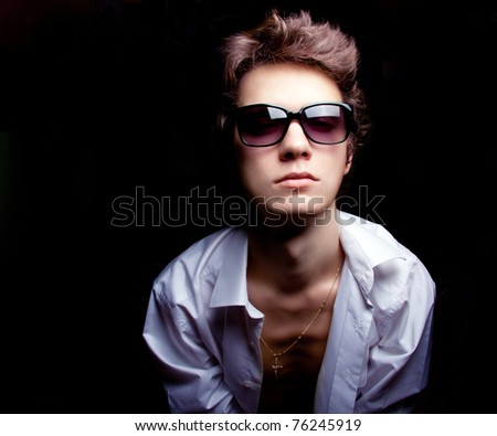 fashion portrait of the young guy dressed in shirt.