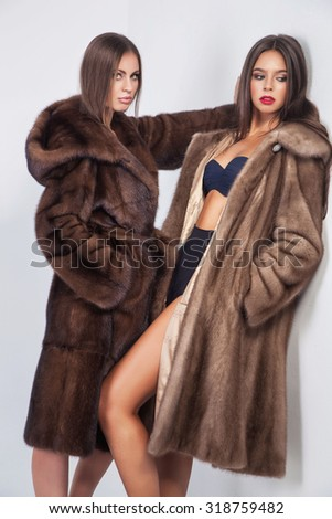 Fashion portrait of two elegant woman in fur mink coat over white background.