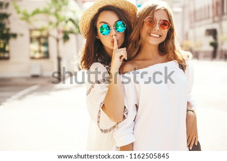 Fashion portrait of two young stylish hippie brunette and blond women in summer hipster dress posing on the street background. Models share secrets, gossip. Finger near mouth