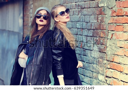 Fashion portrait of two young women in sunglasses. Leather jackets, street fashion