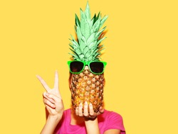 Fashion portrait of woman covering her face with pineapple with sunglasses over a yellow background