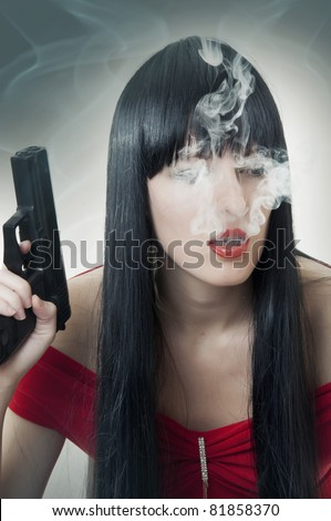 Fashion portrait of woman with handgun and cigarette