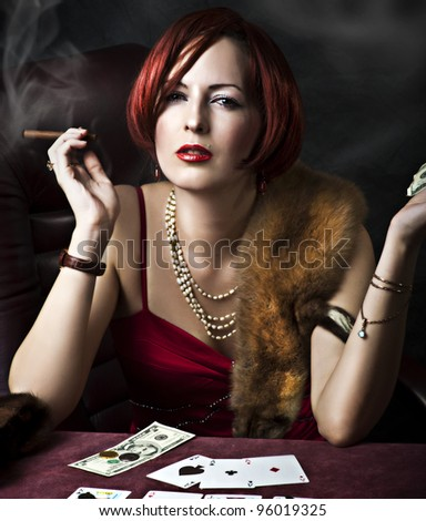 Fashion portrait of young adult woman with red hair in retro style - 30s,50s, 40s years. Player poker or fortune teller