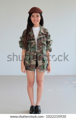 Fashion portrait of Young asian woman wearing Vintage military  Camouflage jacket in a camo print with a US Army patch on the chest