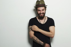 fashion Portrait of young bearded man. Smiling Hipster boy.handsome man in hat.Brutal bearded boy with tattoo