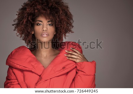 Fashion portrait of young beautiful african american woman with afro hairstyle. Girl with glamour makeup looking at camera, posing in red jacket.