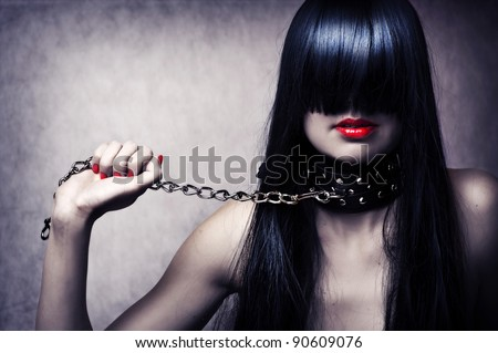 Fashion portrait of young beautiful female model. Glamour woman with long black hair and sexy hairstyle. Lady with leather collar with studs on a metal chain in hand
