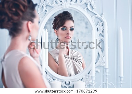 Fashion portrait of young beautiful woman looking in antique mirror, bright makeup and jewelery #170871299
