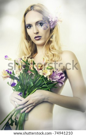 Fashion portrait of young beautiful woman with flowers in hair closeup. Fairy