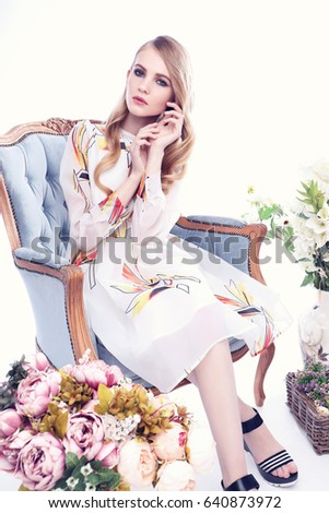 Fashion portrait of young blond woman with flowers. Soft light and colours. Posing in the  studio