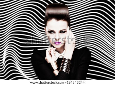 Fashion portrait of young caucasian model with bright makeup on striped black and white background. Beautiful woman with red lips. Glamour trendy accessories and hairstyle