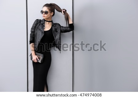 Fashion portrait of young elegant brunette woman outdoor. black leather jacket, clutch bag, sunglasses, choker, black dress