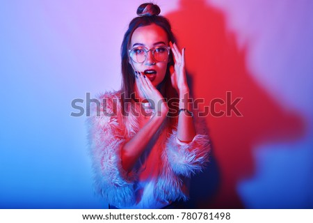 Fashion portrait of young elegant girl in glasses. Colored background, studio shot. Beautiful brunette woman with red lips. hipster girl in neon. Woman with stylish hair surprised.
