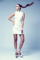 Fashion portrait of young elegant woman. Fashion makeup, white short dress, white shoes, studio shot