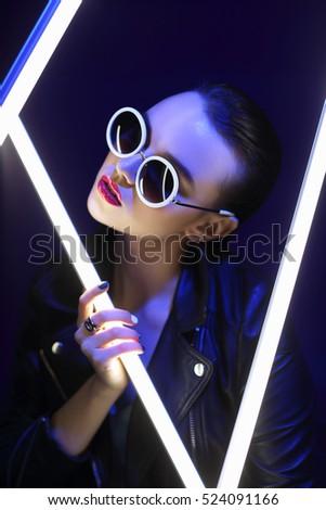 Fashion portrait of young elegant woman in sunglasses. Colored background, studio shot