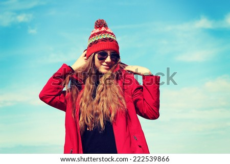 Fashion portrait of young hipster woman with hat and sunglasses on the beach. Photo toned style Instagram filters.