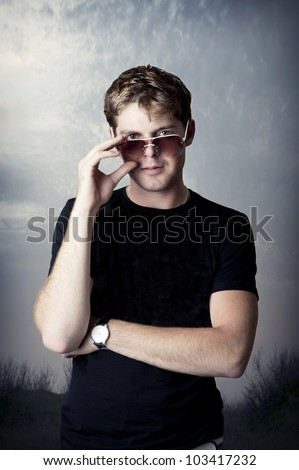 Fashion portrait of young man in fashionable sun glasses