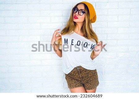 Fashion portrait of young pretty hipster woman with blonde hairs and big full bright lips wearing stylish outfit, denim swag shorts hat glasses and t shirt with funny print.urban wall background.