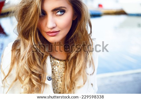 Fashion portrait of young sensual blonde woman with long amazing curled ombre hairs, natural make up.