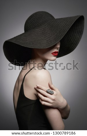 Fashion portrait of young sexy lady with beautiful black hat and evening dress. Stylish elegant woman with modern jewelry. Studio photo of pretty model on grey background. #1300789186