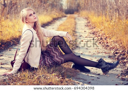 Fashion portrait of young woman outdoor in autumn. Leather jacket, bag, boots, skirt, casual style