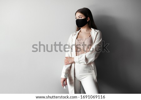 Fashion portrait of young woman wearing a face mask, looking at camera, use antiseptic, isolated on gray background. Flu epidemic, dust allergy,  protection against virus. Corona virus. COVID-19.
