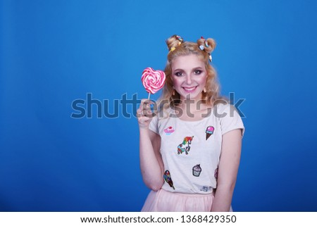 Fashion portrait pretty pretty young woman with pink lips with lollipop heart wearing white wig. Fashionable dress over blue background.