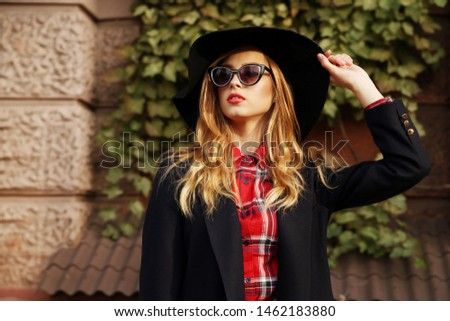Fashion portrait pretty pretty young woman with red lips wearing black hat sunglasses urban style.Girl wearing a coat in the fall