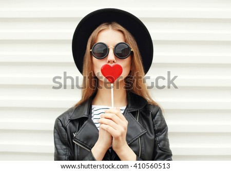 Fashion portrait pretty sweet young woman having fun with lollipop over white background