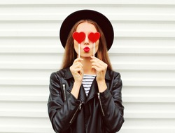 Fashion portrait pretty sweet young woman with red lips making air kiss with lollipop heart wearing black hat leather jacket over white background
