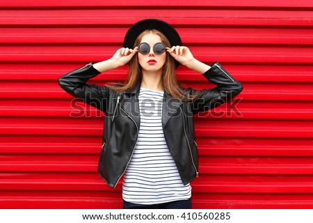 Fashion portrait pretty woman in black rock style over red background