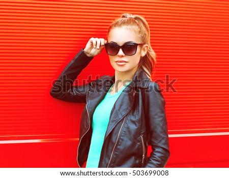 Fashion portrait pretty woman in sunglasses over red background