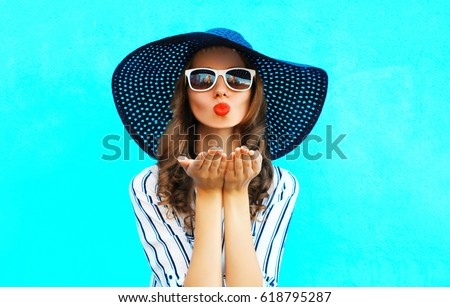Fashion portrait pretty woman with red lips is sends an air kiss in straw summer hat over colorful blue background