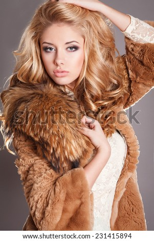 Fashion portrait sexy blond woman in elegant fur coat winter, fashionable girl vogue style. Fashion Beauty girl model with long healthy wavy hair styling.