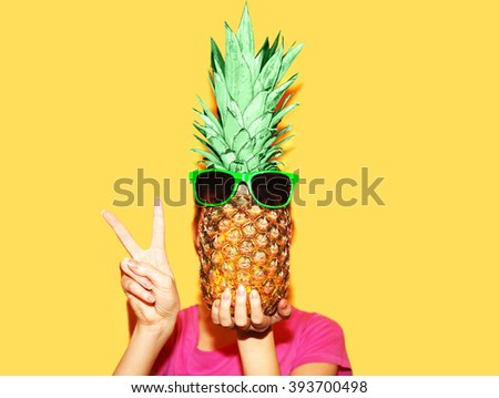 Fashion portrait woman and pineapple with sunglasses over yellow background
