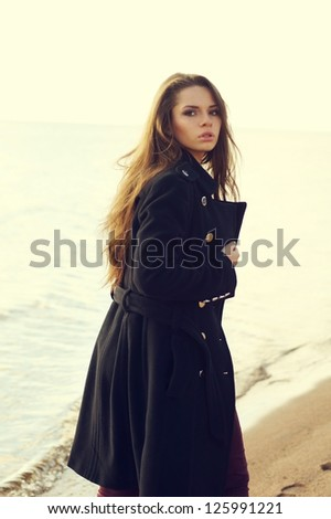 fashion portrait. woman in coat walking at coast and looking in camera backside