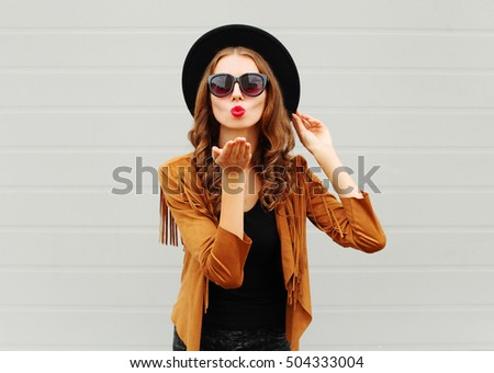 Fashion portrait woman model blowing red lips sends air sweet kiss wearing black hat, sunglasses over urban grey background