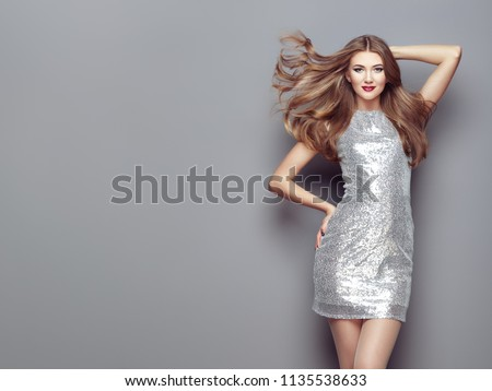 Fashion Portrait young Woman in elegant Silver Dress. Girl with Elegant Hairstyle Posing on a Gray Background. Beautiful Model with Curly Hairstyle