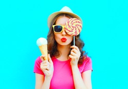 Fashion portrait young woman making an air kiss with lollipop and ice cream over colorful blue background
