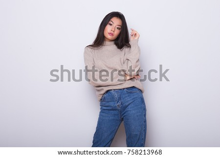 Fashion posing beautiful Asian girl in trendy wearing. Casual wearing in jeans, high heel shoes and sweeter #758213968