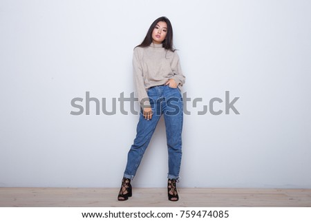 Fashion posing beautiful Asian girl in trendy wearing. Casual wearing in jeans, high heel shoes and sweeter #759474085
