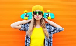 Fashion pretty cool girl with skateboard over colorful orange background